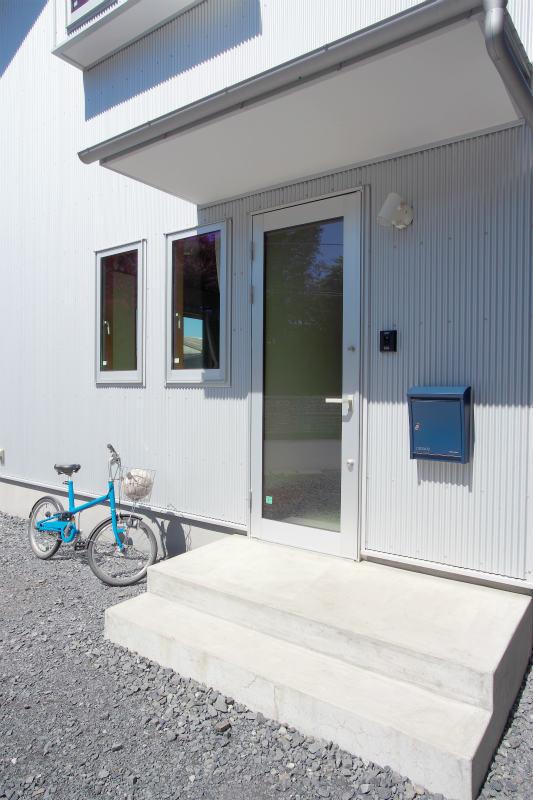 小さな家の玄関ドア。ガラス面を大きく採光を確保する。
